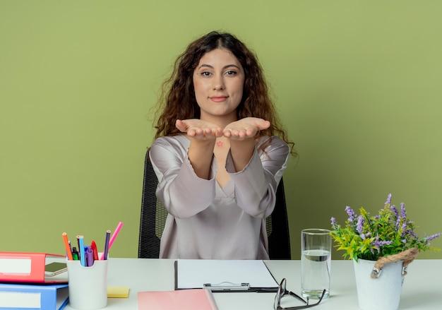 Olhando para a câmera, agradou a jovem e bonita trabalhadora de escritório sentada à mesa com as ferramentas de escritório estendendo as mãos para a câmera isolada no fundo verde-oliva
