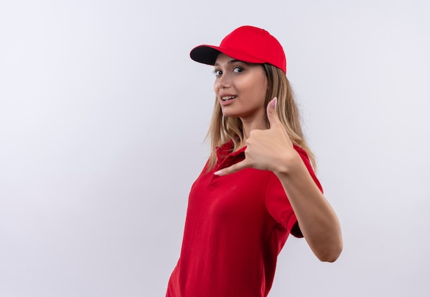 Olhando para a câmera, agradou a jovem entregadora de uniforme vermelho e boné mostrando gesto de ligação isolado no fundo branco