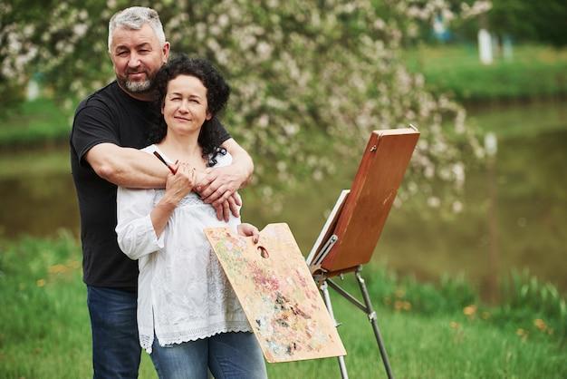 Olhando para a câmera. casal maduro tem dias de lazer e trabalhando na pintura juntos no parque