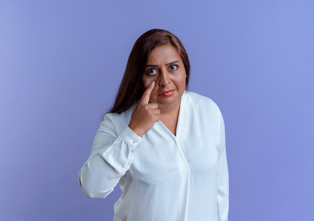Olhando para a câmera, casual caucasiana, mulher de meia-idade colocando o dedo ao redor dos olhos