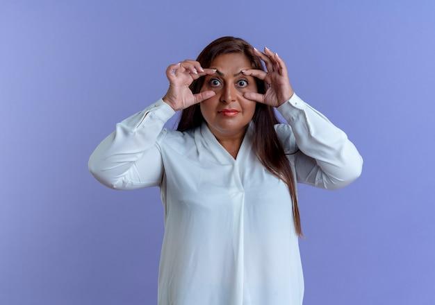 Olhando para a câmera, casual caucasiana, mulher de meia-idade opente com os olhos dos dedos