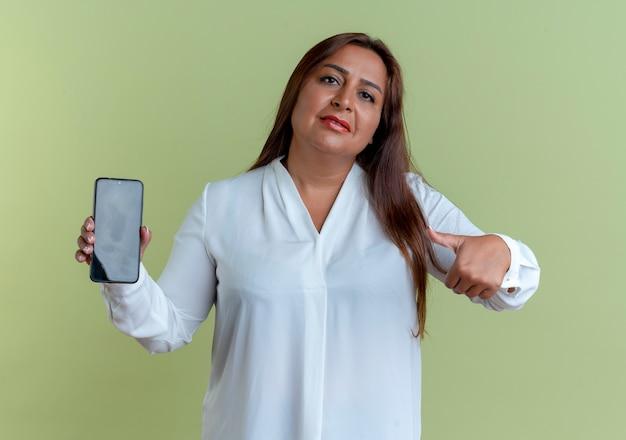 Olhando para a câmera, casual caucasiana, mulher de meia-idade segurando e apontando para o telefone