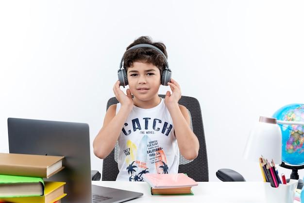 Olhando para a câmera, garotinho usando fones de ouvido, sentado na mesa com ferramentas escolares, colocando a mão em fones de ouvido isolados no fundo branco