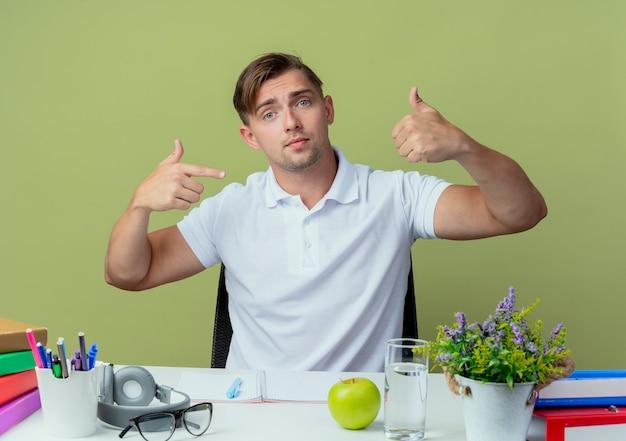 Olhando para a câmera impressionou um jovem estudante bonito sentado à mesa com as ferramentas da escola, o polegar para cima e aponta para o polegar isolado em verde oliva