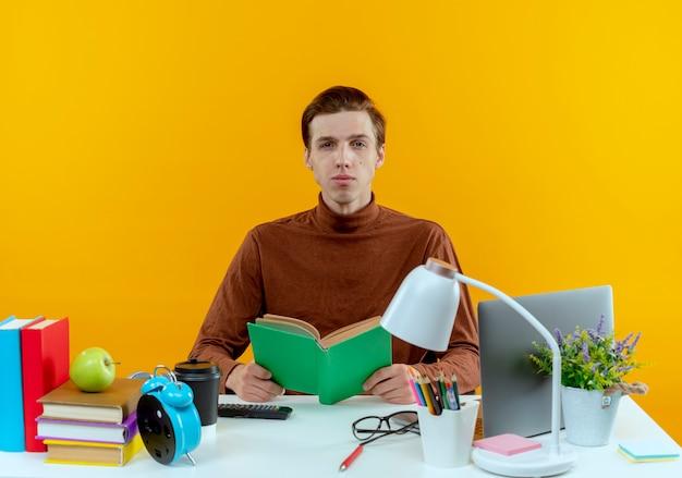 Olhando para a câmera, jovem estudante, sentado na mesa com ferramentas escolares, segurando um livro