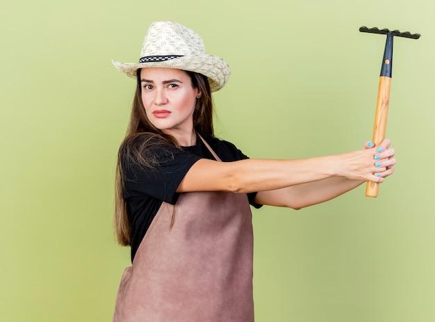 Olhando para a câmera, linda garota jardineira de uniforme usando chapéu de jardinagem segurando um ancinho ao lado isolado em fundo verde oliva