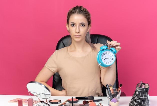 Olhando para a câmera, linda jovem sentada à mesa com ferramentas de maquiagem segurando um despertador isolado na parede rosa