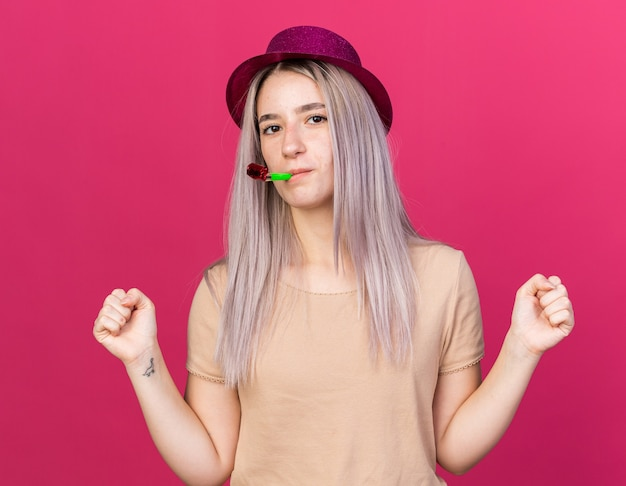 Olhando para a câmera, linda jovem usando chapéu de festa soprando apito de festa mostrando gesto de sim