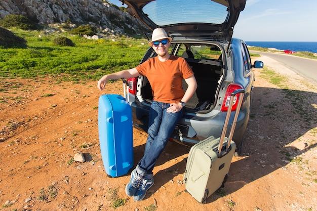Olhando para a câmera, um homem alegre vai passar o fim de semana no carro com a bagagem.