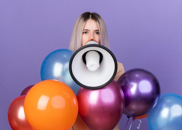 Olhando para a câmera, uma jovem linda em pé atrás de balões fala no alto-falante