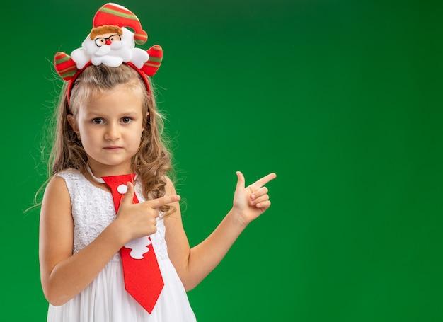 Olhando para a câmera, uma menina usando um aro de cabelo de natal com pontos de gravata na parte de trás, isolado sobre fundo verde