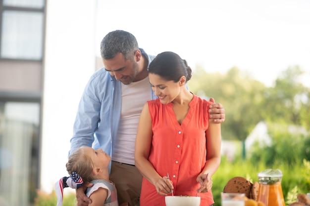 Olhando para a filha. pais olhando para sua adorável filha antes de tomarem o café da manhã ao ar livre