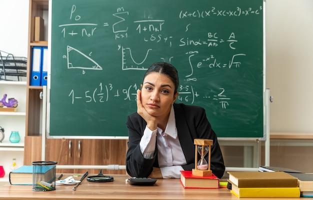 Olhando para a frente, jovem professora sentada à mesa com o material escolar colocando a mão no queixo na sala de aula