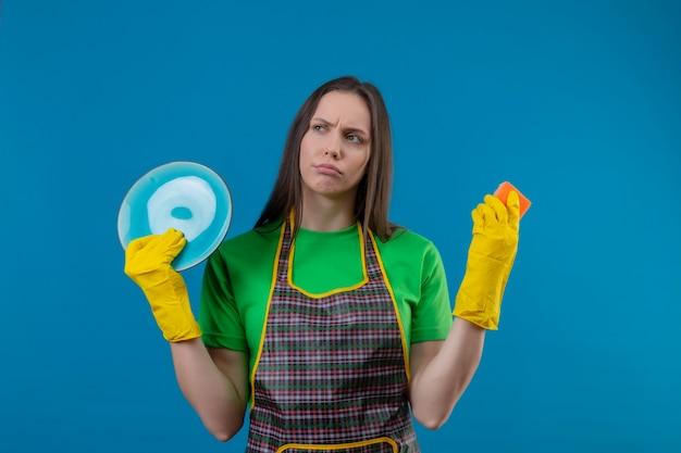 Olhando para a limpeza lateral de uma jovem vestindo um uniforme com luvas, segurando um prato e uma esponja na parede azul isolada