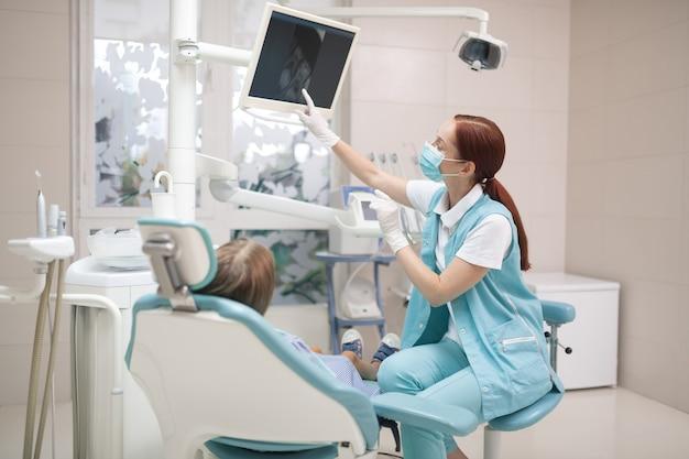 Olhando para a tela. menina olhando para a tela enquanto dentista profissional ruivo fazendo radiografias