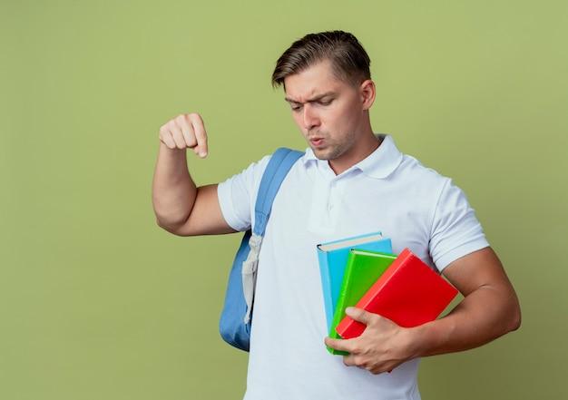 Olhando para baixo preocupado com o jovem bonito estudante do sexo masculino vestindo uma bolsa com livros e apontando para baixo isolado em fundo verde oliva
