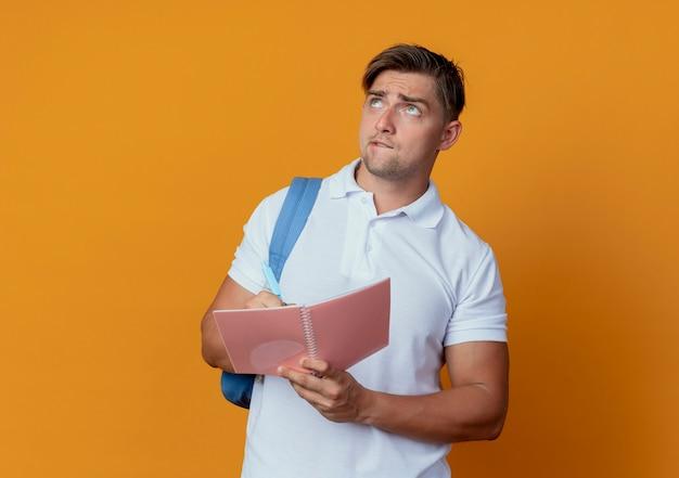 Olhando para cima confuso jovem estudante bonito do sexo masculino usando uma bolsa com o caderno e uma caneta isoladas em um fundo laranja