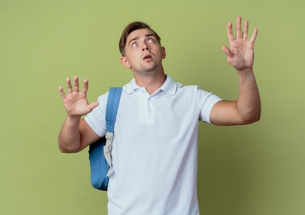 Olhando para cima, jovem bonito e preocupado estudante do sexo masculino usando uma bolsa de costas espalha as mãos isoladas sobre fundo verde oliva