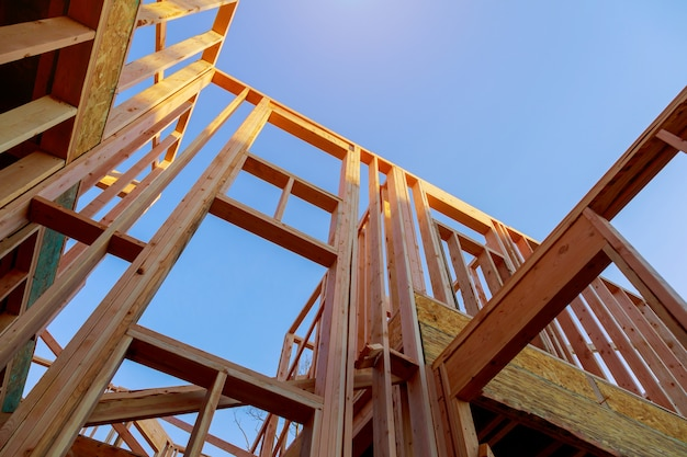 Olhando para cima novas vigas de construção sob um céu azul claro com luz solar