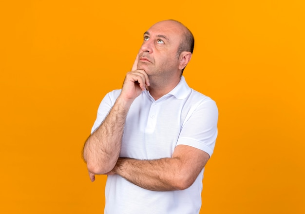 Olhando para cima pensando em um homem maduro casual colocando a mão no queixo