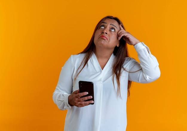 Olhando para cima, pensando em uma mulher casual caucasiana de meia-idade segurando o telefone e colocando o dedo na testa