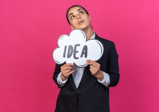 Olhando para cima, uma jovem linda usando um blazer preto segurando uma bolha de ideias