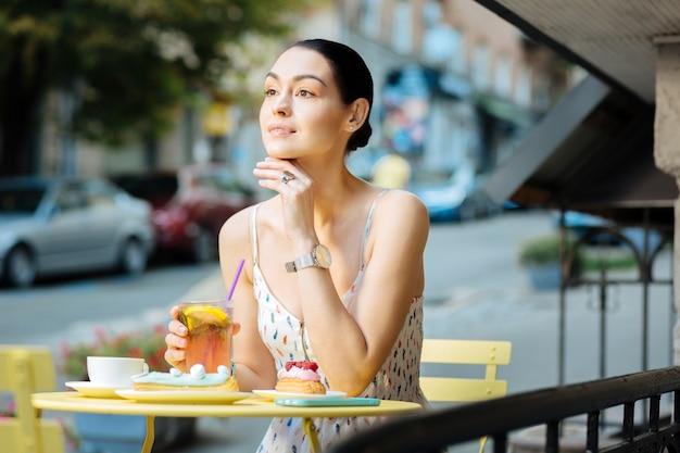Olhando para longe. bela jovem olhando para longe e sorrindo enquanto está sentada à mesa com um copo de limonada