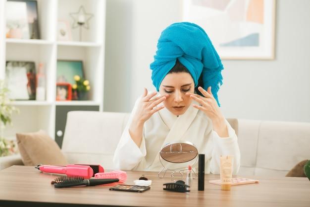 Olhando para o espelho, jovem enrolada no cabelo em uma toalha, aplicando creme de tonificação, sentada à mesa com ferramentas de maquiagem na sala de estar