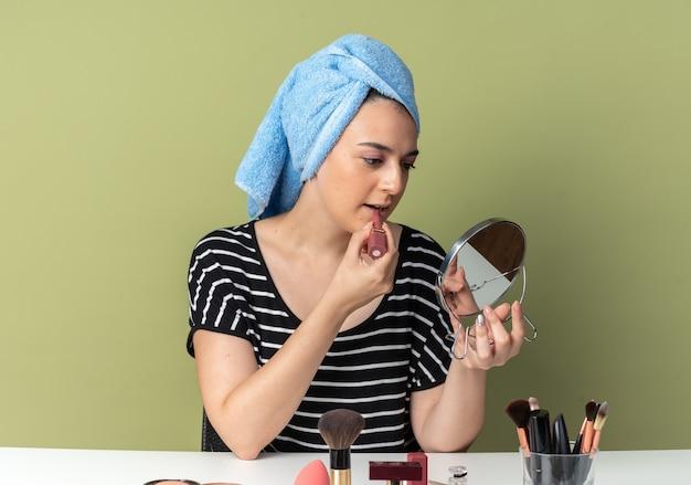 Olhando para o espelho, jovem linda se senta à mesa com ferramentas de maquiagem enroladas em uma toalha, aplicando batom isolado na parede verde oliva