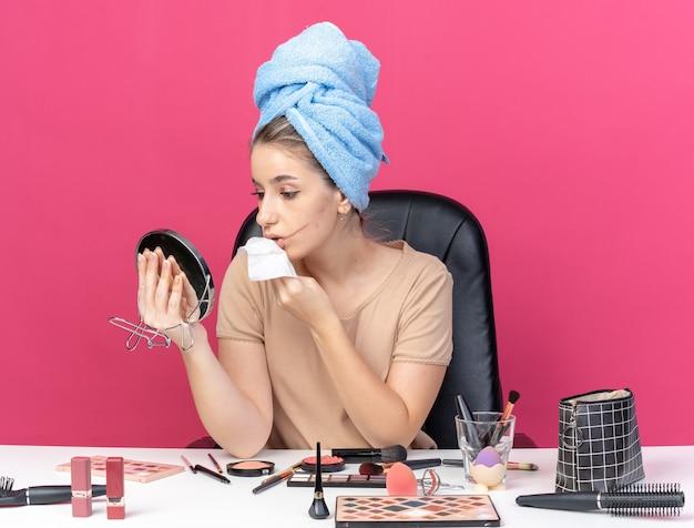 Olhando para o espelho, jovem linda se senta à mesa com ferramentas de maquiagem enroladas em uma toalha no cabelo, limpando o rosto com um guardanapo isolado na parede rosa