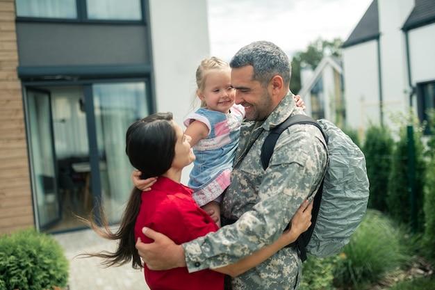 Olhando para o herói. esposa de cabelos escuros olhando para seu herói e se sentindo feliz após reunião familiar