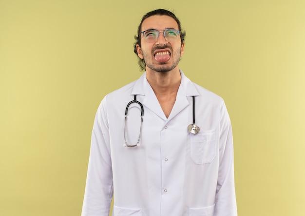 Olhando para o jovem médico com óculos ópticos, túnica branca com estetoscópio mostrando a língua