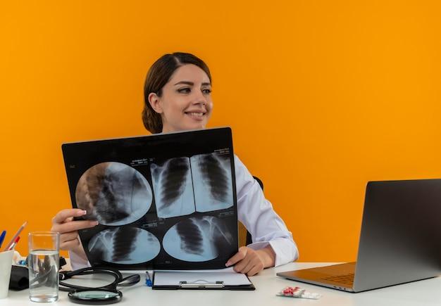 Olhando para o lado amiling jovem médica vestindo bata médica com estetoscópio sentada na mesa de trabalho no computador com ferramentas médicas segurando um raio-x na parede amarela de isolamento