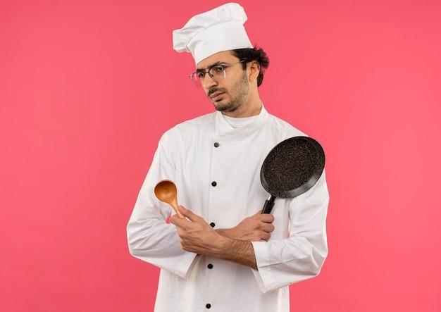 Olhando para o lado confuso, jovem cozinheiro vestindo uniforme de chef e óculos segurando e cruzando a colher com a frigideira