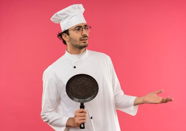 Olhando para o lado confuso, jovem cozinheiro vestindo uniforme de chef e óculos segurando uma frigideira e apontando para os lados