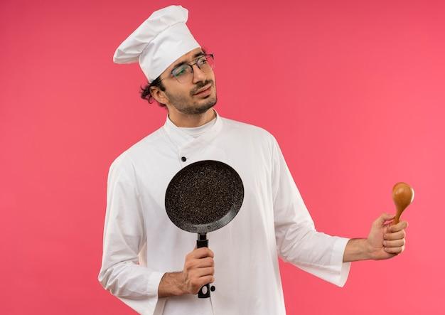 Olhando para o lado confuso, jovem cozinheiro vestindo uniforme de chef e óculos segurando uma frigideira e uma colher