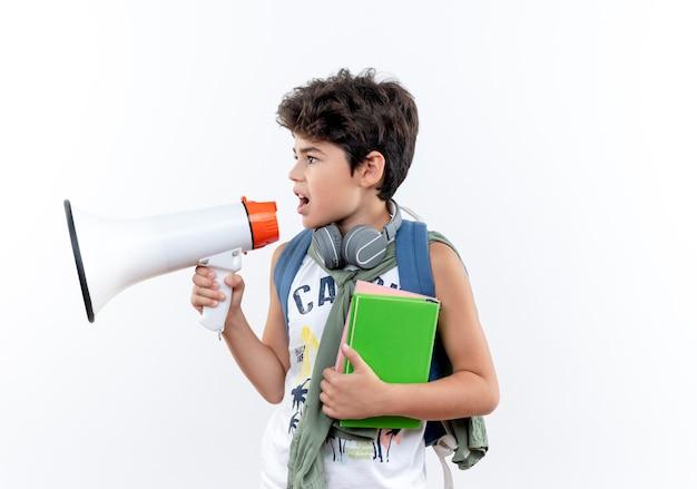 Olhando para o lado, garotinho usando mochila e fones de ouvido segurando um livro e falando no alto-falante