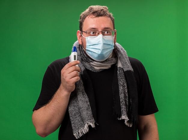 Olhando para o lado, homem doente de meia-idade usando máscara médica e lenço segurando um termômetro