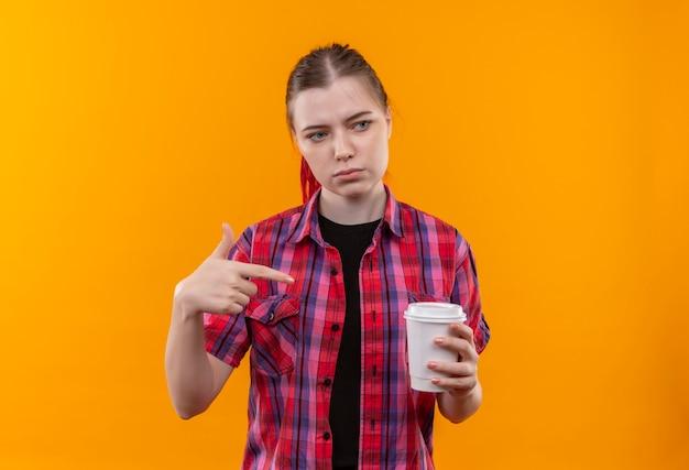 Olhando para o lado, jovem e linda garota vestindo camisa vermelha aponta o dedo para a xícara de café em sua mão sobre fundo amarelo isolado