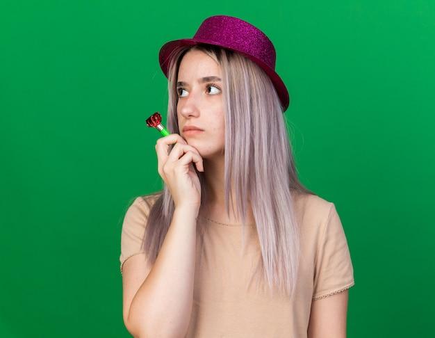 Olhando para o lado, jovem e linda mulher usando um chapéu de festa segurando um apito de festa e colocando a mão sob o queixo isolado na parede verde