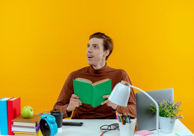 Olhando para o lado, jovem estudante satisfeito sentado à mesa com ferramentas escolares segurando um livro