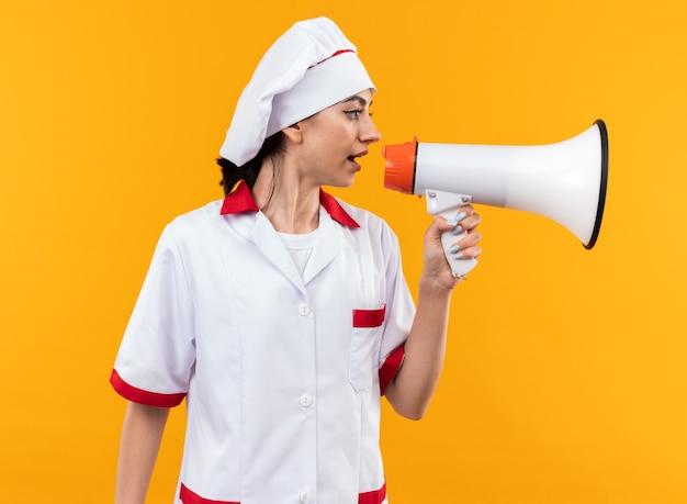 Olhando para o lado, jovem linda com uniforme de chef fala no alto-falante isolado na parede laranja