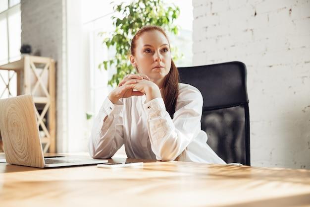 Olhando para o lado. mulher jovem caucasiana em traje de negócios, trabalhando no escritório. jovem empresária, gerente fazendo tarefas com smartphone, laptop, tablet tem conferência online. conceito de finanças, trabalho.