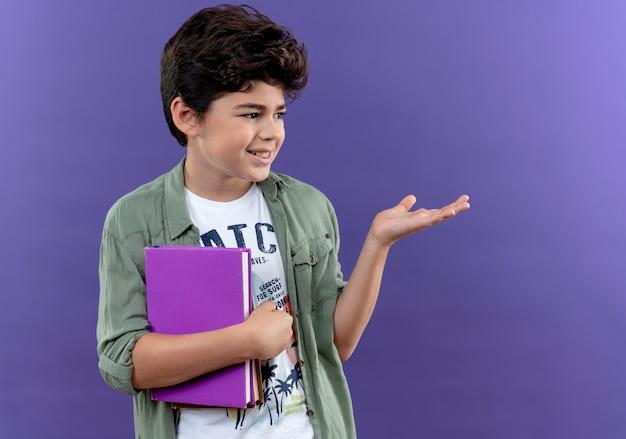 Olhando para o lado, o pequeno aluno satisfeito segurando o livro e apontando as mãos