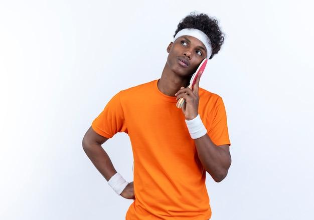 Olhando para o lado, pensando em um jovem afro-americano esportivo usando bandana e pulseira, colocando uma raquete de pingue-pongue na bochecha isolada no fundo branco
