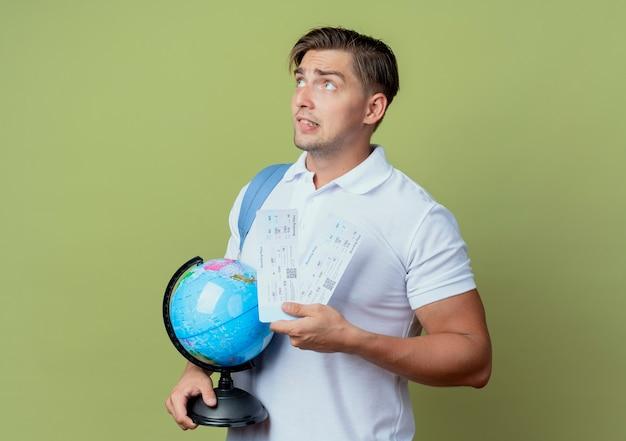 Olhando para o lado, pensando em um jovem bonito estudante do sexo masculino vestindo uma bolsa com os ingressos e um globo isolado no fundo verde oliva