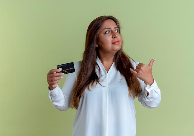Olhando para o lado, pensando em uma mulher casual caucasiana de meia-idade segurando um cartão de crédito e mostrando um gesto de ligação