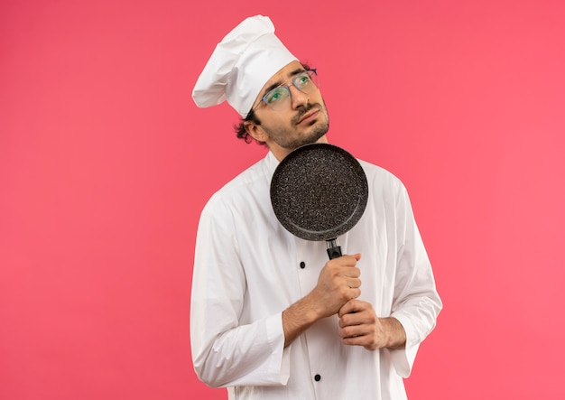 Olhando para o lado pensando jovem cozinheiro vestindo uniforme de chef e óculos segurando uma frigideira em volta do queixo
