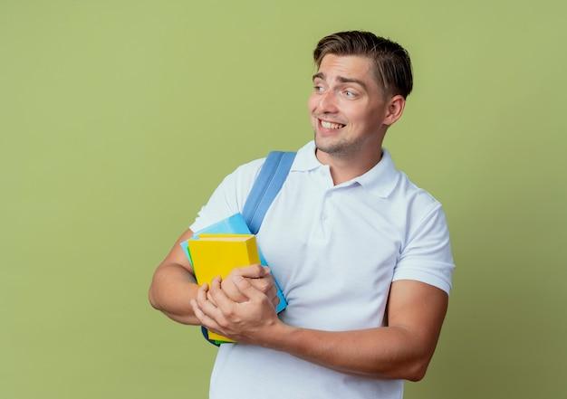 Olhando para o lado preocupado, jovem bonito estudante do sexo masculino usando uma bolsa de costas segurando livros isolados sobre fundo verde oliva