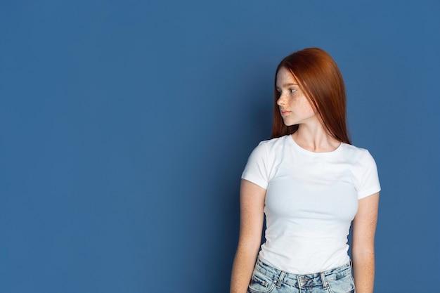 Olhando para o lado. retrato de uma jovem caucasiana na parede azul